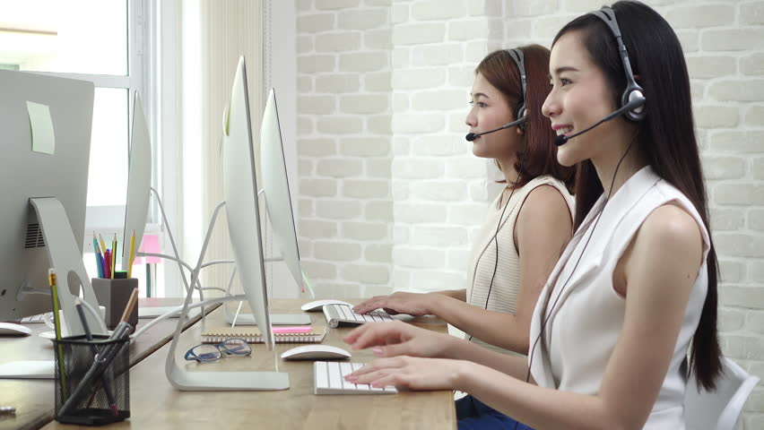 Smiling beautiful young Asian businesswoman telemarketing customer service agent team working and talking with a friendly helpful attitude in call center