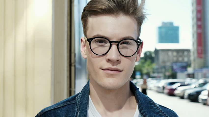 Portrait of happy cute caucasian man smiling in city. Close-up. Handsome young man with glasses looking at camera and smiling | Shutterstock HD Video #31836064