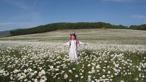 Girl dressed in traditional Ukrainian clothes dancing among daisies.