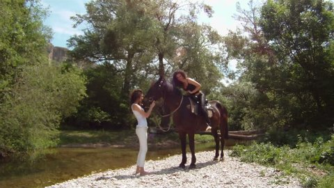 Two women learning to ride ahorse.