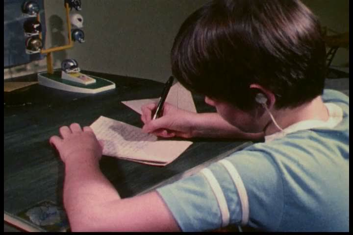 CIRCA 1970s - A boy plays football, writes to Washington Redskins professional football player Lawrence Brown and, later, he departs with his sister to mail the letter, in 1977. | Shutterstock HD Video #31841848