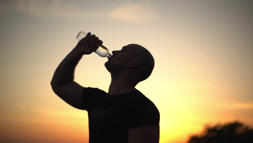 closeup slow motion side view silhouette of caucasian bald muscular guy drinking water from plastic bottle, after doing workout on nature with colourful sunrise background #31843825