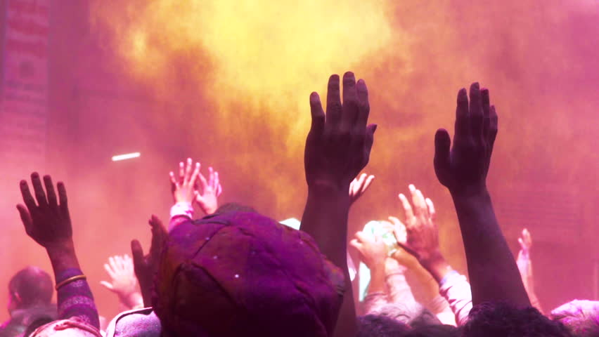 Graded & ungraded: Praying hands in colorful powder paint crowd at holy Hindu Holi Festival temple celebration in India - Slow motion closeup