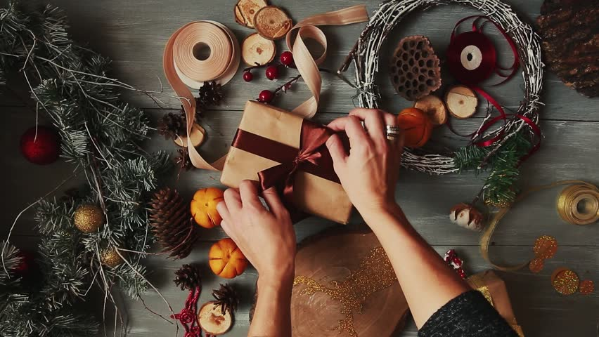A top-down plan. Fully visible the table with the decorations. Female hands put and finalize Christmas gift wrapped in craftool paper on a wooden table. Bandaging tape and tied in a bow. #31854595