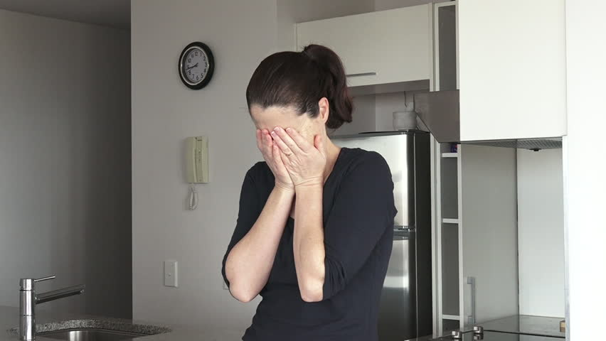 An upset adult woman in her thirties (30s) crying in her home kitchen. Woman problems concept.Real People. Copy space. Slider motion.