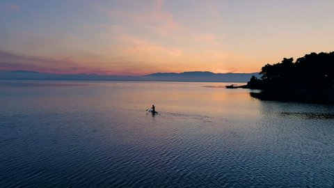 Aerial Shot of a Beautiful Woman with on a Standup Paddleboard. Woman Silhouette with Pink Sunset and Coastal Hills Visible. Shot on Phantom 4K UHD Camera.