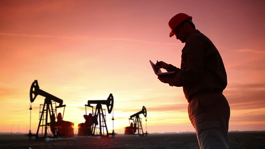 Oil Industry Pump jack with one oil worker who using a phone and typing on laptop.In a background are Silhouettes of three Pump jack at sunset light.
