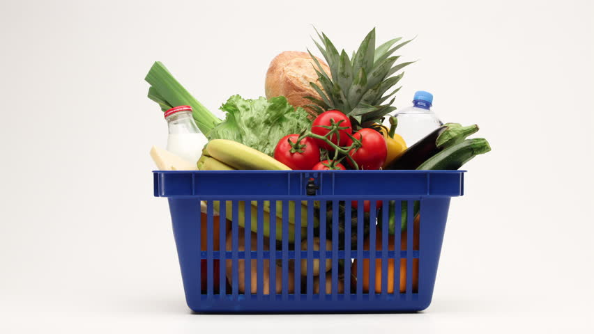 Side view on shopping basket filled with vegetables, bread and milk products moving on white background. 4K stop motion animation.