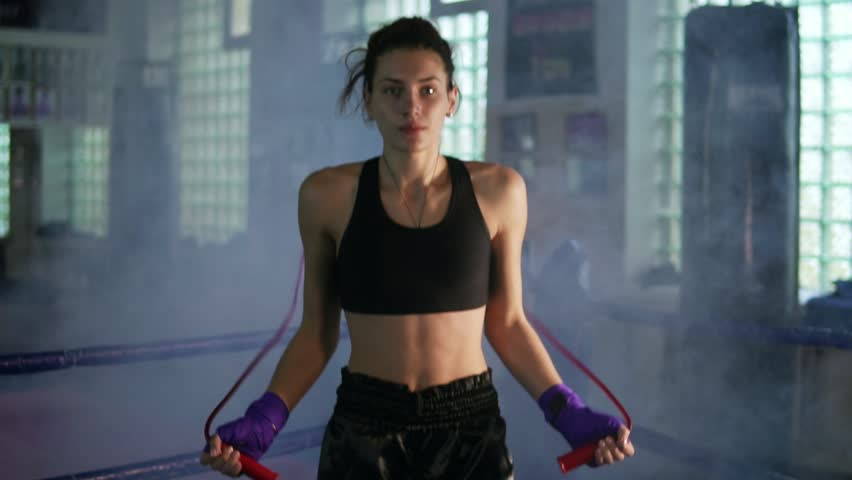 Young female boxer with her hands wrapped in bandage jumping on the skipping rope in a gym with smoke. Slowmotion shot