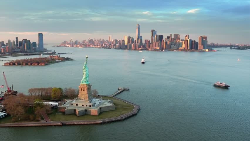 Aerial view of the Statue of Liberty at dusk. Manhattan and New Jersey skyline. New York City, United States. Shot from a helicopter. | Shutterstock HD Video #31885084
