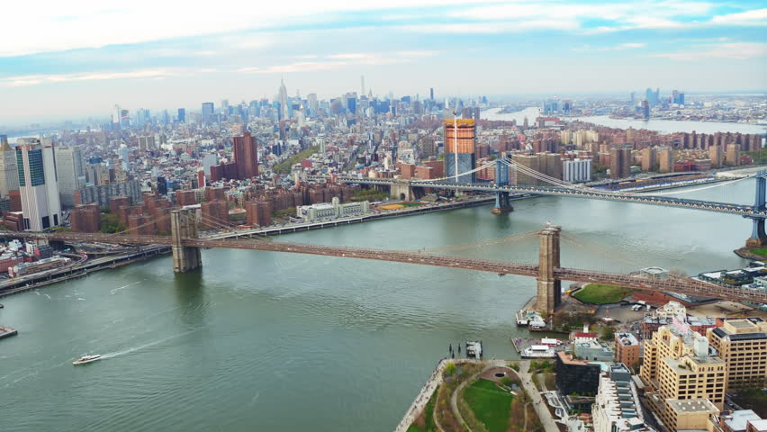 Aerial view of the Brooklyn and Manhattan Bridge in NY. Cityscape and famous skyscrapers in the Financial District and midtown Manhattan. Shot from a helicopter. | Shutterstock HD Video #31885156