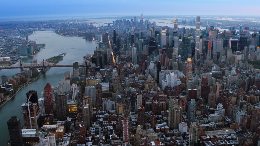 Aerial shot of Midtown Manhattan, 59th Street Bridge and Roosevelt Island. Famous skyscrapers and traffic passing by 1st avenue. Dusk in New York City, United States. Shot from a helicopter.