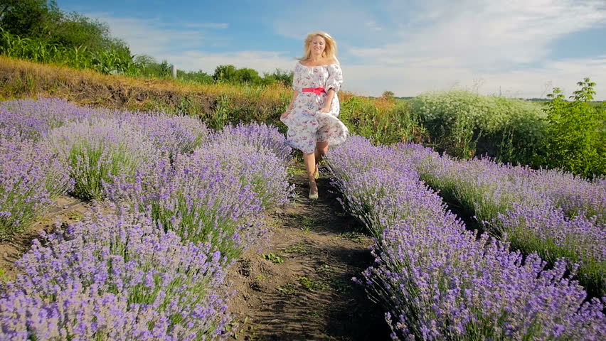 Slow motion video of happy cheerful blonde woman in dress running and jumping at lavender field #31887433