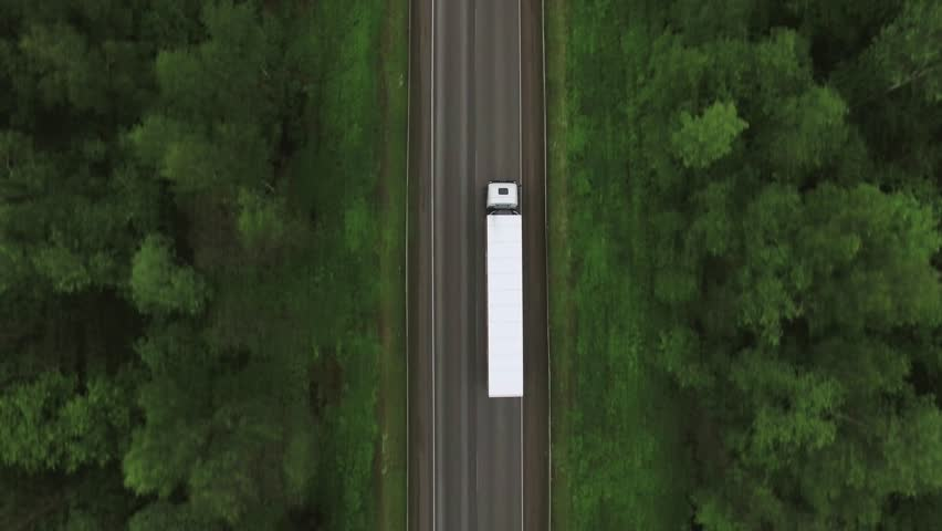 Trucks driving / traveling on the forest asphalt road aerial footage / top view / Highway truck traffic