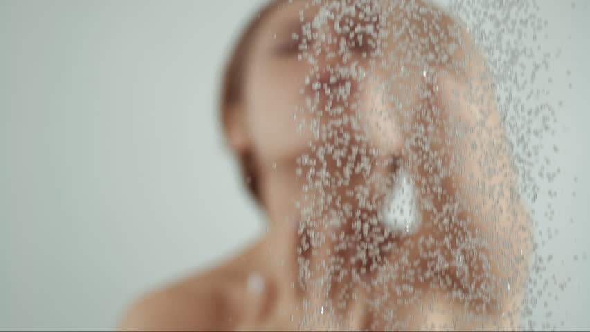 Woman taking a shower in slow motion, beautiful girl washing and enjoy herself under a shower, close up of hands, chest and body details