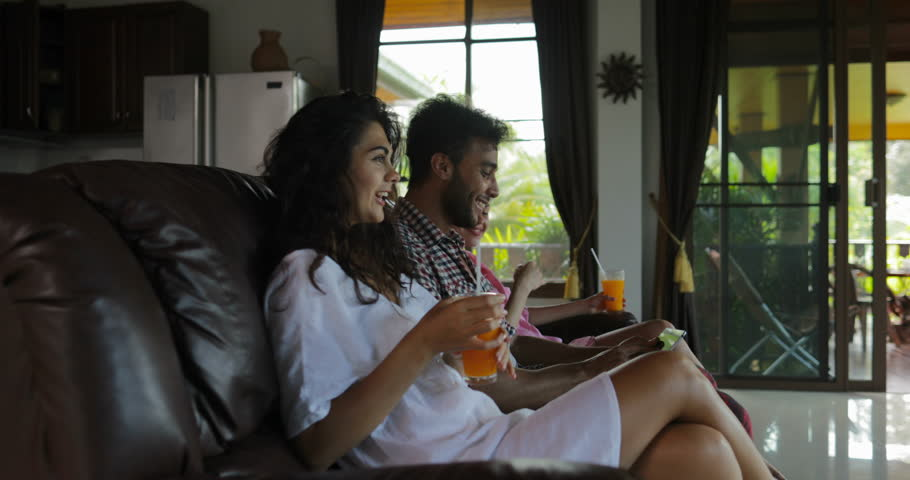 People Use Tablet Computer On Coach Watching Tv In Living Room Drink Juice, Young Man And Woman Group In Morning Talking Modern Apartment Interior Slow Motion 60 | Shutterstock HD Video #31902541