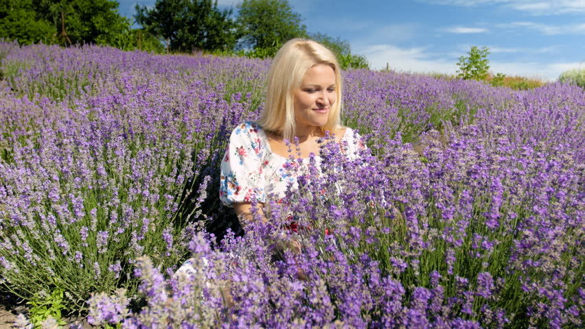 4k footage of beautiful young woman breathing in aroma of lavender flowers in field #31913029