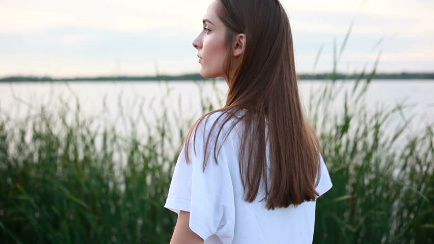 Emotions, lifestyle, beauty, people, 4k concept - Portrait of a young attractive brunette female in a white T-shirt on the waterfront and smiling on the sunset. than turns to camera and smiles | Shutterstock HD Video #31922293