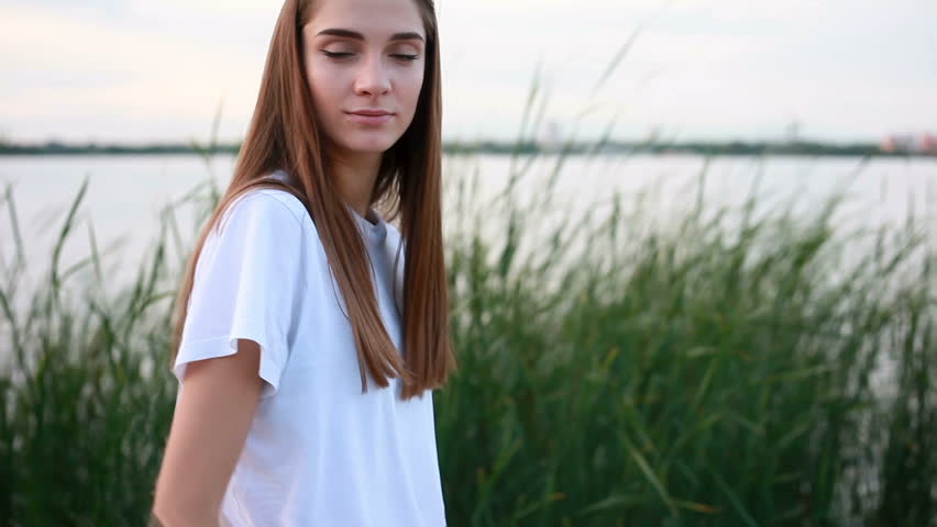 Emotions, lifestyle, beauty, people, slow motion, 4k concept - Portrait young attractive brunette female white T-shirt waterfront and smiling on the sunset. than turns to camera and smiles | Shutterstock HD Video #31922419