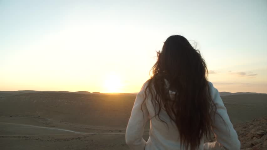 Young woman lift her hands in the air during a desert sunset   Shutterstock HD Video #31923499