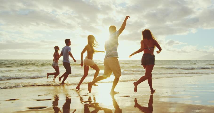 Friends having fun running down the beach at susnet