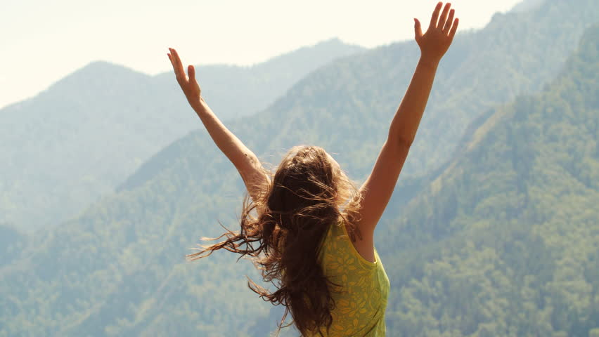Beautiful woman standing on top of mountain and stretching out hands