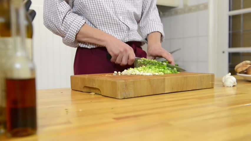 Zooming in on a man's hands, cutting spring onions on a cutting board, #3195973