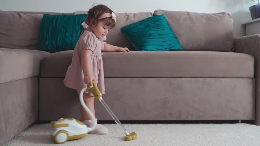 Cute little baby girl using toy vacuum cleaner in room
