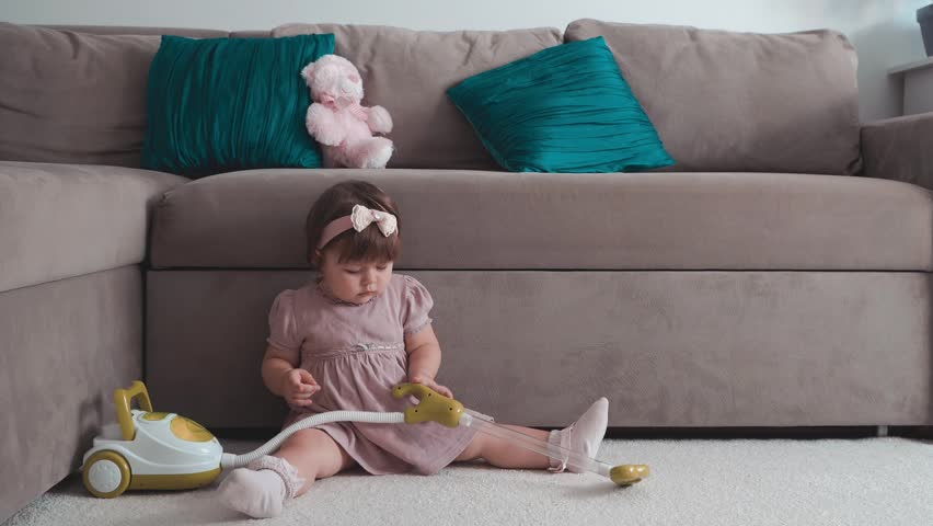 Cute little baby girl using toy vacuum cleaner in room | Shutterstock HD Video #31966696