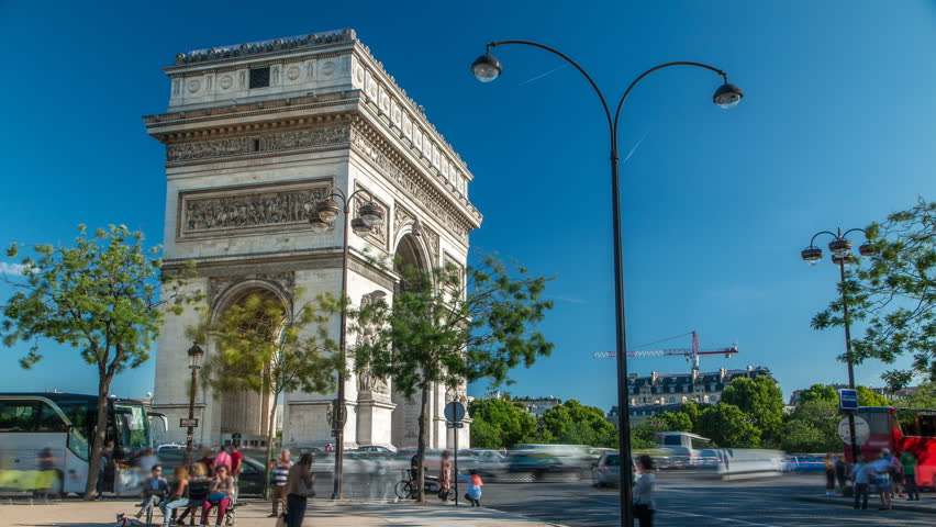The Arc de Triomphe (Triumphal Arch of the Star) timelapse is one of the most famous monuments in Paris, standing at the western end of the Champs-Elyseees. Traffic on circle road. Blue sky at summer
