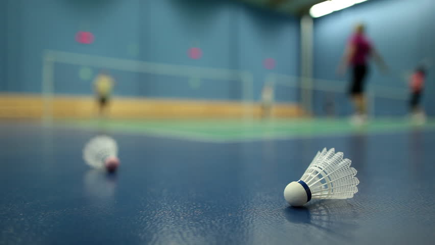 Badminton - badminton courts with players competing; shuttlecocks in the foreground (shallow DOF)