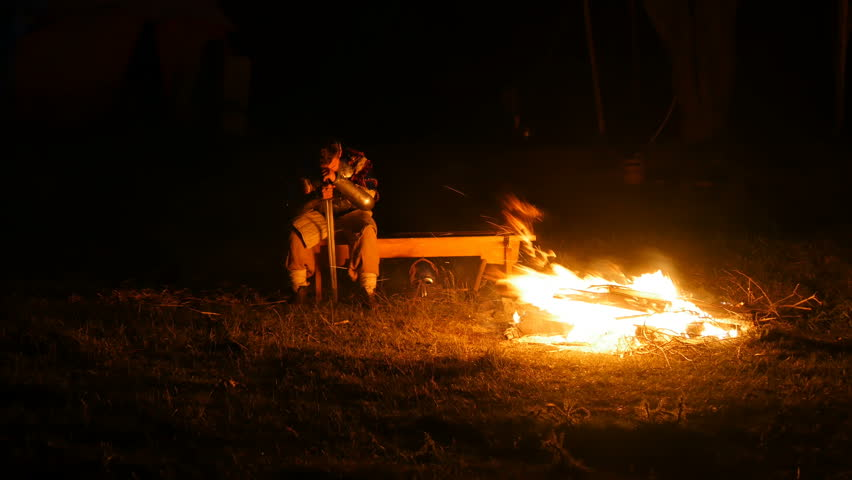 Viking camp. The Viking fell asleep by the fire. Night in Rusich camp. Camp medieval knights.
