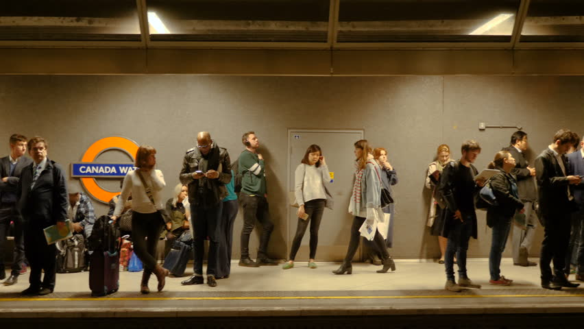 London, United Kingdom - October 20, 2017: Smooth slow motion slider camera shot of people standing and waiting for underground train in Canada Water station in London, UK