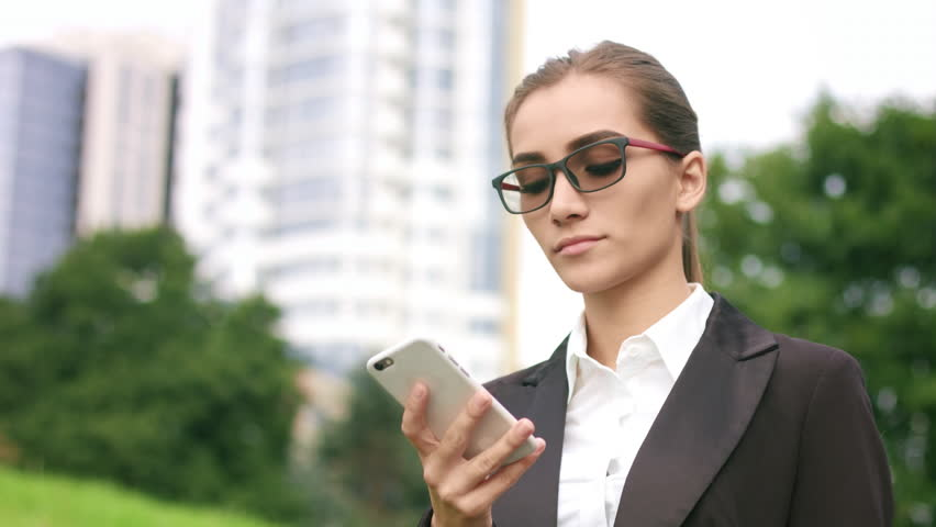 Young attractive businesswoman making phone call outdoors on park and city buildings background | Shutterstock HD Video #31999570