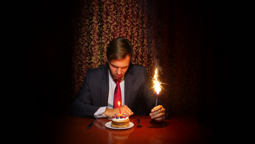 A lone man celebrates a holiday, he sits alone at a table with a cake and a candle. 4k, slow motion