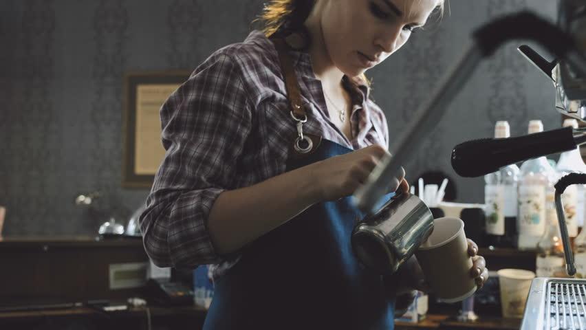Barista pouring milk for cappuccino