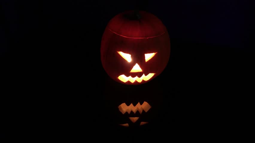 Halloween pumpkin jack o lantern with scary face with a burning candle and reflection | Shutterstock HD Video #32007712