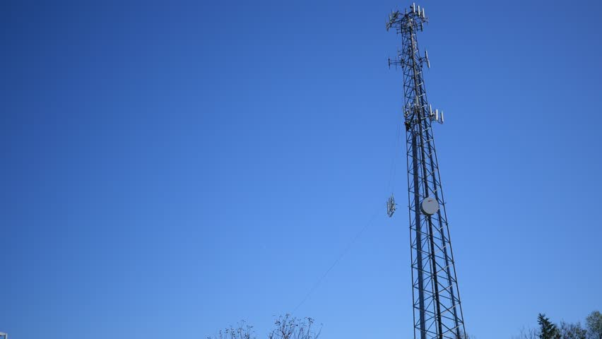 A satellite dish is lifted up onto a radio tower during the day   Shutterstock HD Video #32010157