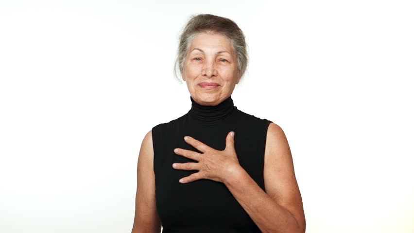 elder serene woman with white tied hair looking at camera smiling with hand on chest thanking over white background in slowmotion. Concept of emotions #32011351
