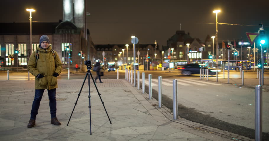 Cinemagraph - Timelapse shot of people and car traffic in the street with a man stocker making footage of night city. Crossroad near Helsinki Central railway station, Finland