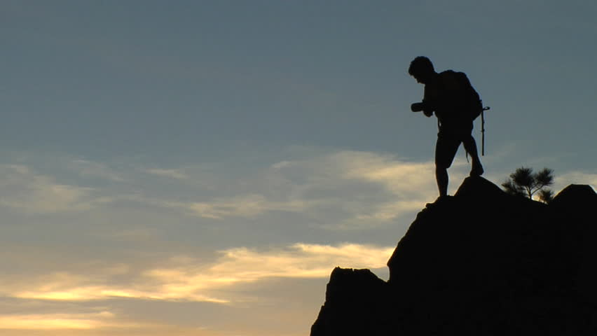 Silhouette of a man with a backpack taking pictures of nature on rocky terrain in the mountains of the American wilderness | Shutterstock HD Video #3201463