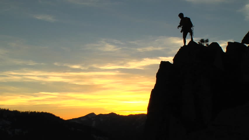 Silhouette of a man with a backpack taking pictures of nature on rocky terrain in the mountains of the American wilderness | Shutterstock HD Video #3201502