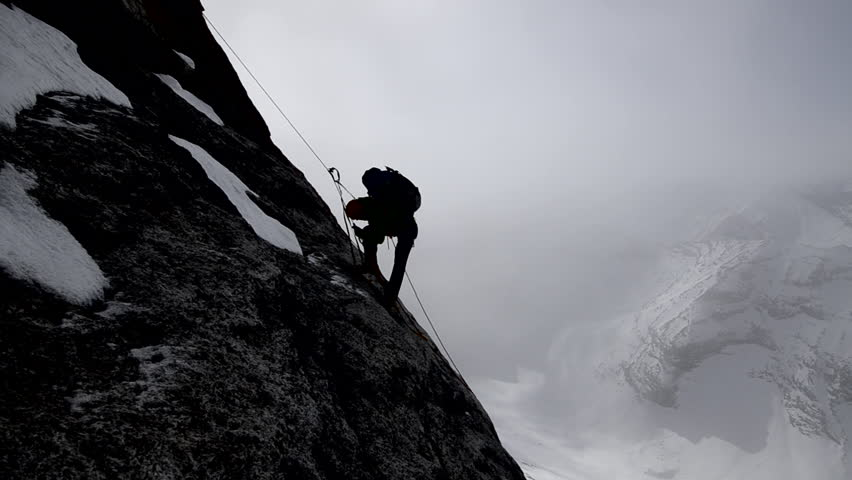 Silhouette of a climber with a backpack ascending a sheer rock face on his way to a mountain peak in the Alaskan wilderness during the day   Shutterstock HD Video #3201658