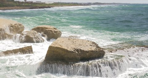 Landscape with Rosh Hanikra coast and strong waves of turquoise sea crushing white chalk rocks