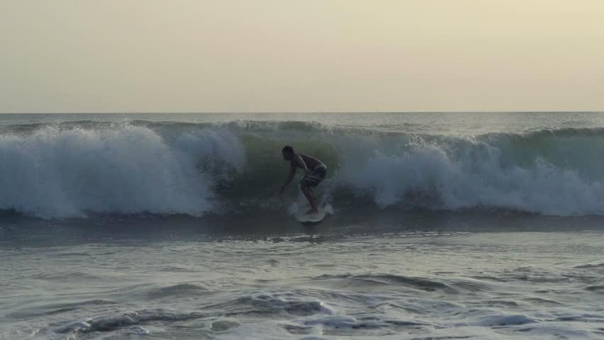 INDONESIA, Bali 15.07.2017: Man surfing in sea, super slow motion 240fps     Shutterstock HD Video #32020000