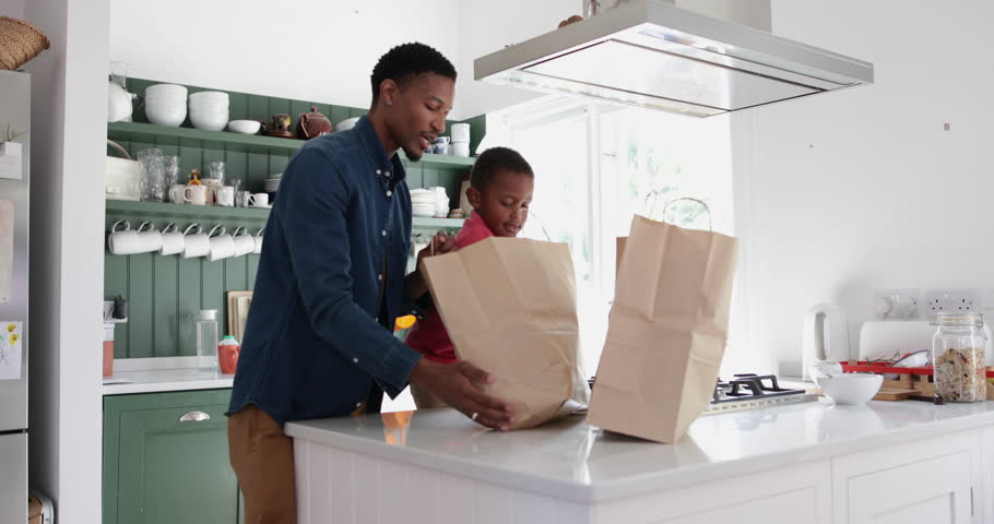 Boy helping Father unpack groceries