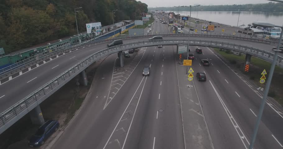 Aerial survey. Kiev-road junction. October 15, 2017. A large number of cars drive along the highway. City landscape, road with cars near the river Dnieper. Period of the year is autumn, cloudy day. | Shutterstock HD Video #32032615