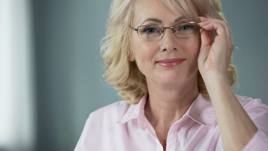 Nice middle-aged woman putting on glasses smiling into camera, healthy eyesight