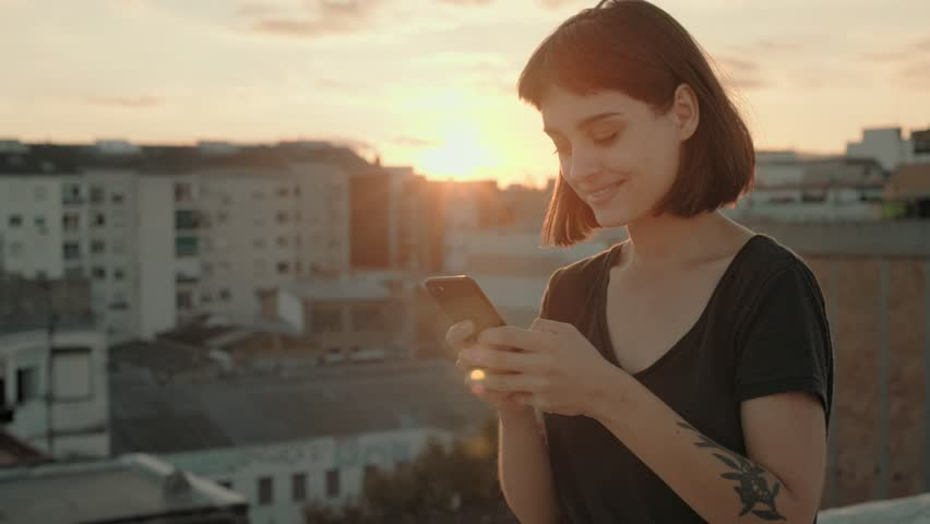 Pretty young woman, stands on rooftop in middle of big megapolis city during orange sunset summer evening. She is hipster and trendy with artisan tattoos, chats on smartphone and looks into camera
