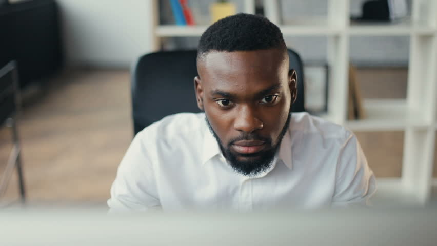 African American handsome male uses computer for work in modern office programmer serious looks at monitor screen freelance successful worker businessman solves engineering problems Slow motion Royalty-Free Stock Footage #32044096